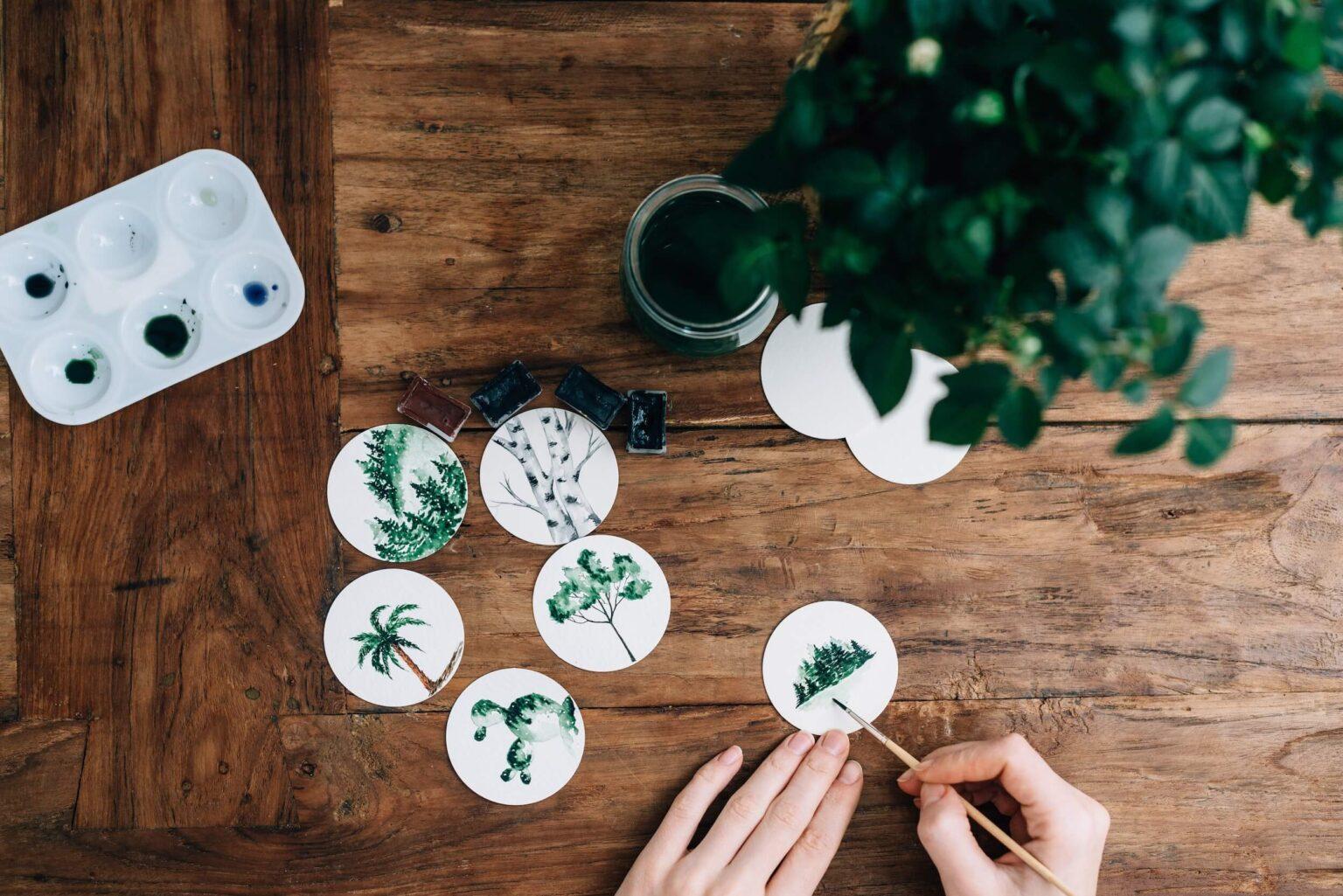 Kobieta maluje farbami naturę na okrągłym papierze